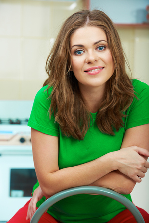 contemporary living room: Close up woman face against home kitchen background. Clothes of green color. Portrait of smiling female model. Stock Photo