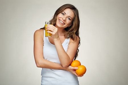 smiling young woman singlet wearing holding orange juice glass and fruit Stock Photo
