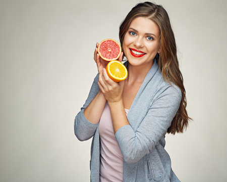 smiling woman holding half orange and grapefruit. isolated studio portrait.