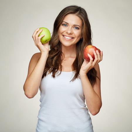 glimlachende vrouw met gezonde tanden die rode en groene appelen houden. wit hemd. geïsoleerd portret. Stockfoto