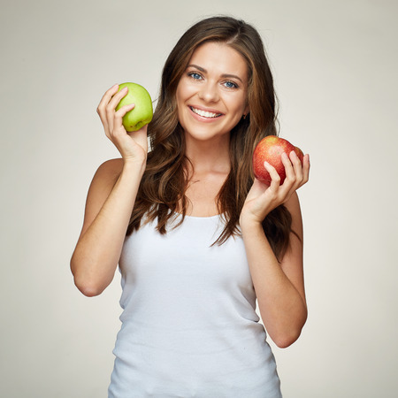 smiling woman with healthy teeth holding red and green apples. white undershirt. isolated portrait. Foto de archivo