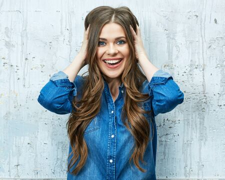Smiling young woman portrait against gray wall. Long hair.