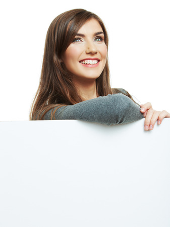 sheet: Smiling woman leaning on big blank board . Close up female face portrait with arms on blank card.