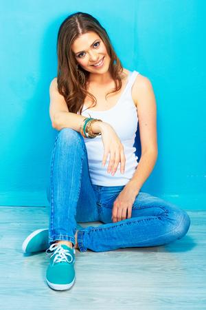 Hipster meisjeszitting op vloer tegen blauwe achtergrond.