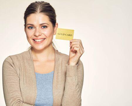 happy woman holding gold credit card. isolated studio portrait. Фото со стока