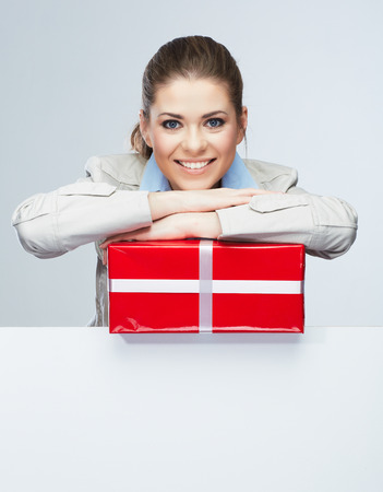sheet: Corporate bonus concept . Smile Business woman hold red gift box, portrait with blank white board on gray isolated . Female smiling model .