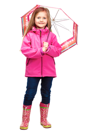 Little girl posing in fashion style wearing autumn clothing. Rubber boots.