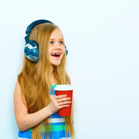 Grappig klein vrouwelijk model met hoofdtelefoons die zich tegen witte achtergrond met rode koffiekop bevinden, glas. Lang blond haar.