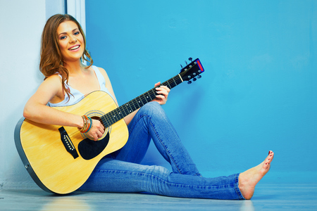 teenager girl guitar play . young model with long hair sitting on a floor.