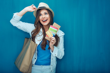 Travel concept portrait of happy woman tourist. Girl holding passport with credit card and ticket. Stock Photo