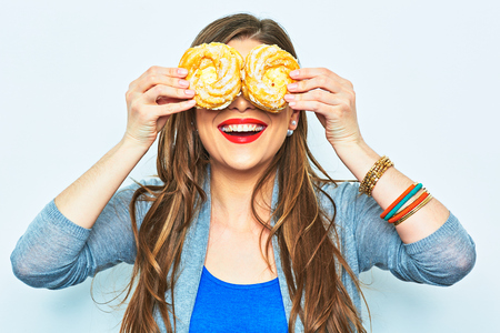 Woman smile with teeth. Two cake. Diet concept. Lon hair model. Stock Photo