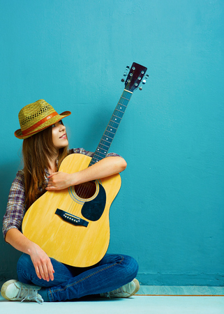 Fashion model girl country style dressed seating with guitar. Young woman.