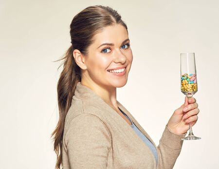 Smiling young woman holding vitamin cocktail in glass. Healthy lifestyle concept portrait.