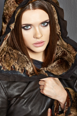 Portrait of young woman in Fur leather clothes.