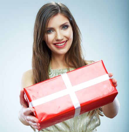 Portrait of beautiful smiling woman in evening dress hold red gift box. Isolated studio background female model.