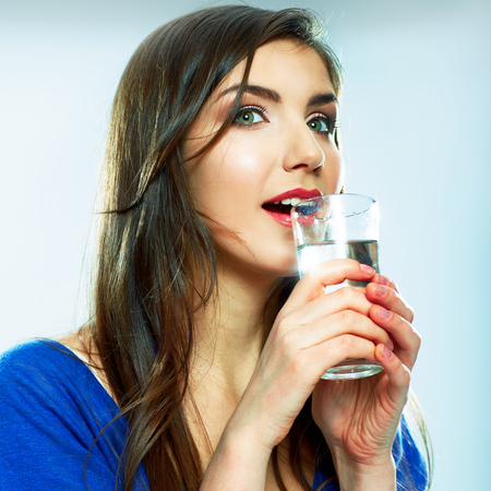 Beautiful Woman drinking water from glass. Smiling model.