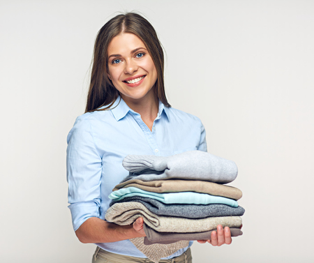 Smiling woman holding stack of warm winter clothes. Portrait isolated on white.