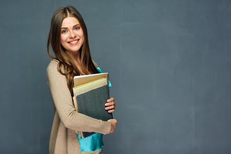 Smiling girl student or woman teacher portrait on gray wall. Imagens