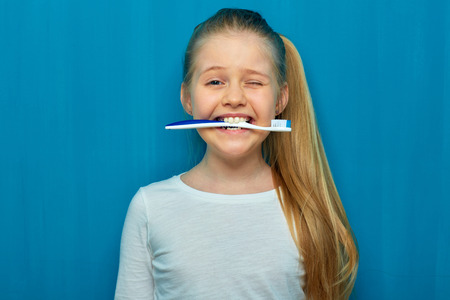 Little girl holding toothy brush with teeth. Blue wall background. 版權商用圖片