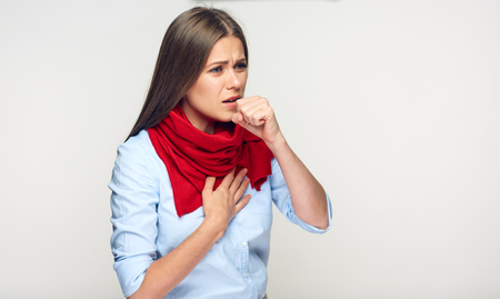 Sickness woman coughing in fist. Portrait of illness girl wearing red scarf.