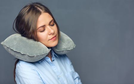 Woman with closed eyes resting with travel pillow. Isolated portrait. Foto de archivo
