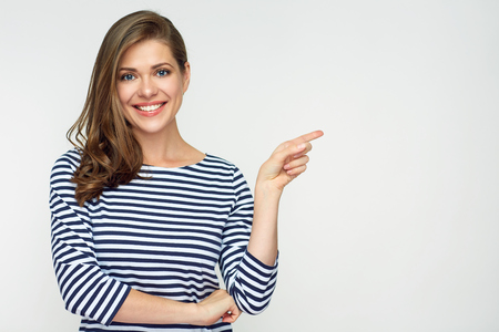 Smiling woman pointing finger side. Isolated portrait on white.
