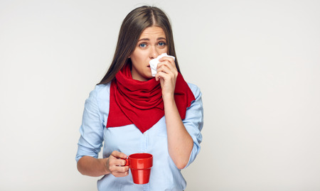 Sickness woman holding red cup blow up nose in paper tissue. Isolated portrait on white.