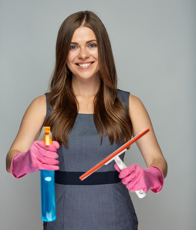 Woman holding windows cleaner in spray bottle. Isolated studio portrait.
