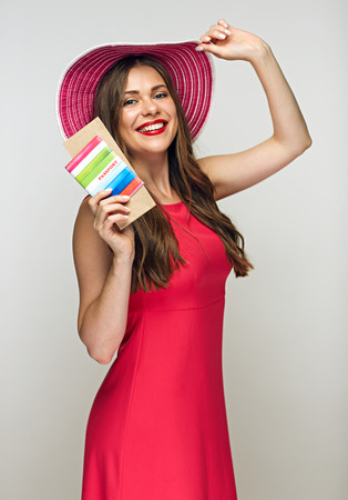 Smiling woman wearing big summer hat and red dress touching her hat and holding passport with ticket. Ready for travel.