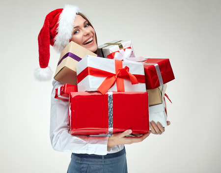 Isolated portrait of businesswoman wearing christmas santa hat holding big many of gift boxes. Фото со стока