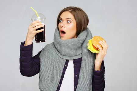 Woman shocked fast food meal. Girl holdin burger with cola drink. Stock Photo
