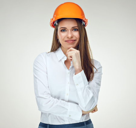 Portrait of thinking business woman wearing builder helmet isolated on white. Stock Photo
