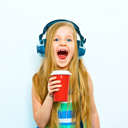 Little screaming girl standing against white background with red coffee cup, glass. Headphones on head. Isolated. Stockfoto