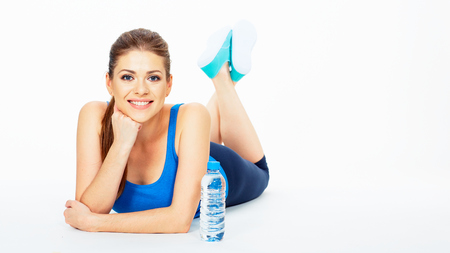 portrait of smiling woman in sport style lying on a floor resting between fitness exercise . white background isolated .