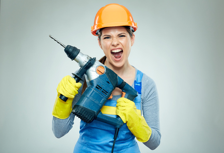 Hard work of woman builder with drill tool. Emotional isolated portrait.