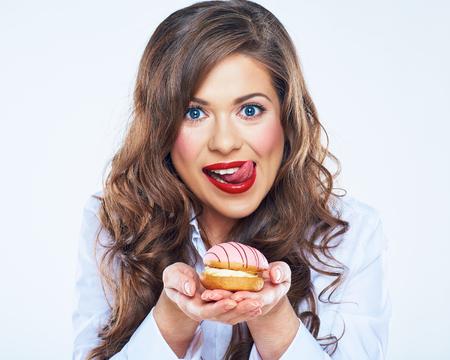 Frau leckte die Lippen mit Kuchen. Lustige Frau. Mädchen mit langen lockigen Haaren.