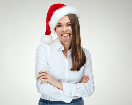 Santa girl standing with crossed arms and showing tongue against white background.