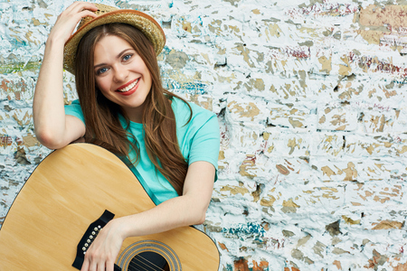 Portrait of young toothy smiling woman with guitar against brick grunge wall.