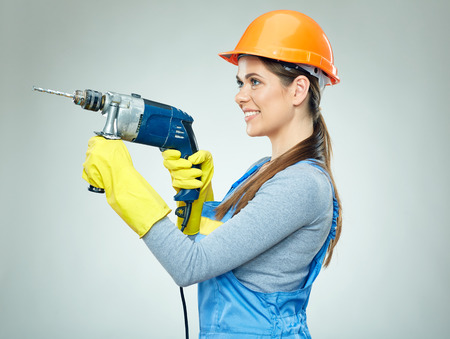 Smiling woman builder wearing protect helmet and uniform holding drill tool. Isolated on gray.