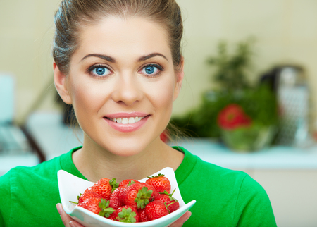 Smiling woman eating strawberry. Close up female face portrait. Healthy mel on a plate Stock Photo