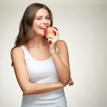 smiling woman bites red apple. healthy teeth. isolated portrait. 版權商用圖片