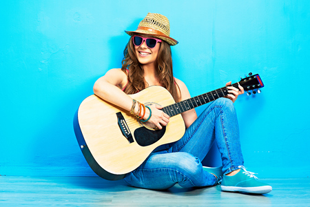 Teenager girl guitar play sitting on a floor. Blue wall  background. Country style.