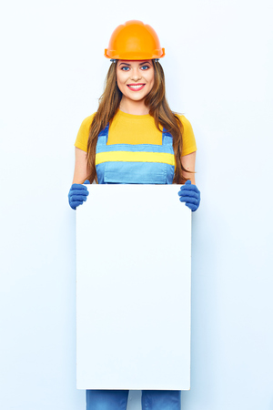 Smiling woman builder coverall dressed holding big board for advertising sign. White Sign board. Stock Photo