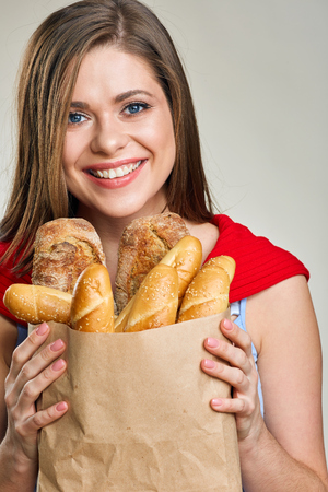 Smiling woman holding bag with bread. Close up isolated female face portrait.