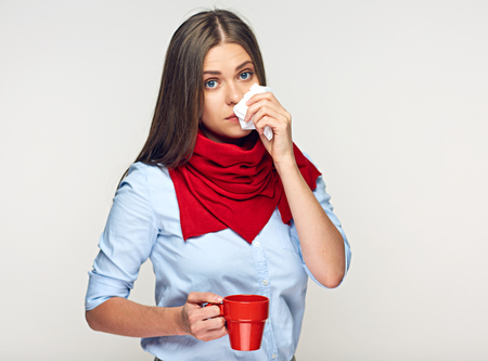 Sick woman blows nose in handkerchief. Red coffee cup. Isolated portrait.