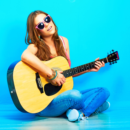 young woman sings and playing guitar . sitting against blue