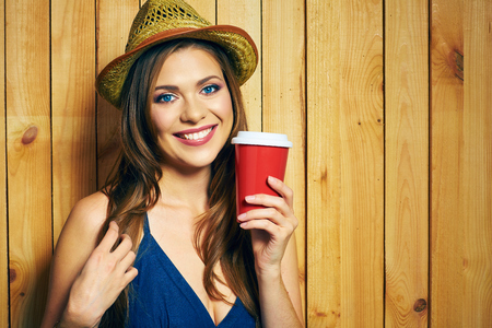 Smiling Young Woman Holding Coffee Cup. Yellow hat. Teeth smiling model with long hair posing on yellow wooden background. 版權商用圖片