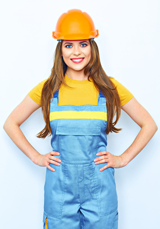 Smiling woman builder helmet dressed. Woman in coverall uniform. Stock Photo