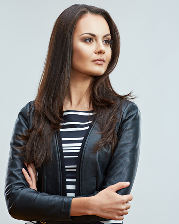 Beautiful woman with long hair dressed in leather jacket. Studio portrait.