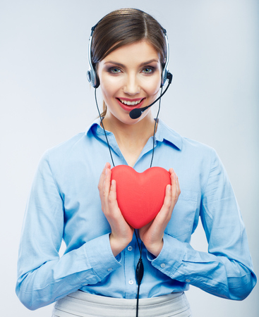 Woman call center operator hold love symbol of Valentine day. Red heart. Close up business woman portrait.